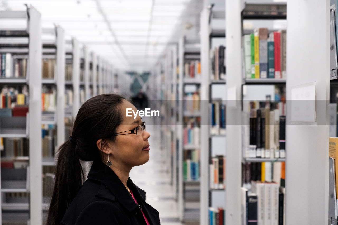 Side View Of Young Woman Looking Books In Shelf At Library