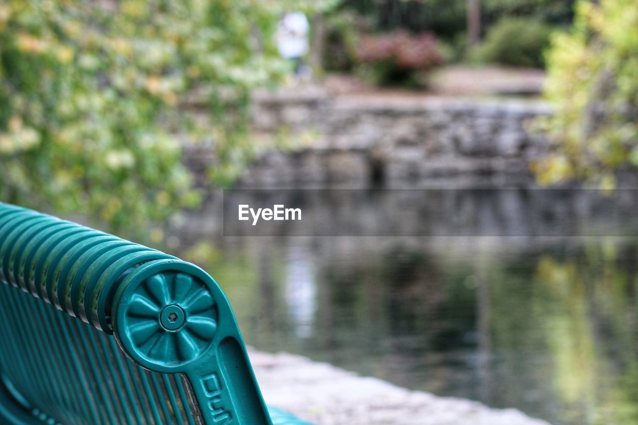 focus on foreground, day, no people, close-up, nature, metal, built structure, green color, outdoors, water, architecture, selective focus, solid, wall, blue, pattern, absence, plant, rock, stone wall, park bench
