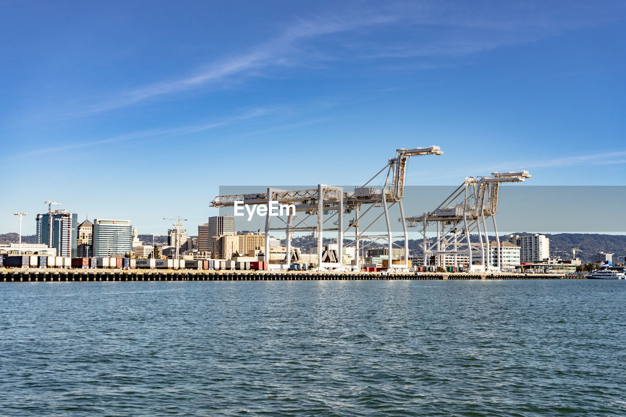 water, waterfront, sky, architecture, industry, crane - construction machinery, nature, machinery, business, sea, built structure, no people, day, building exterior, blue, city, transportation, outdoors, nautical vessel, construction equipment