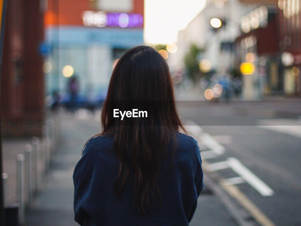 REAR VIEW OF WOMAN WALKING IN CITY