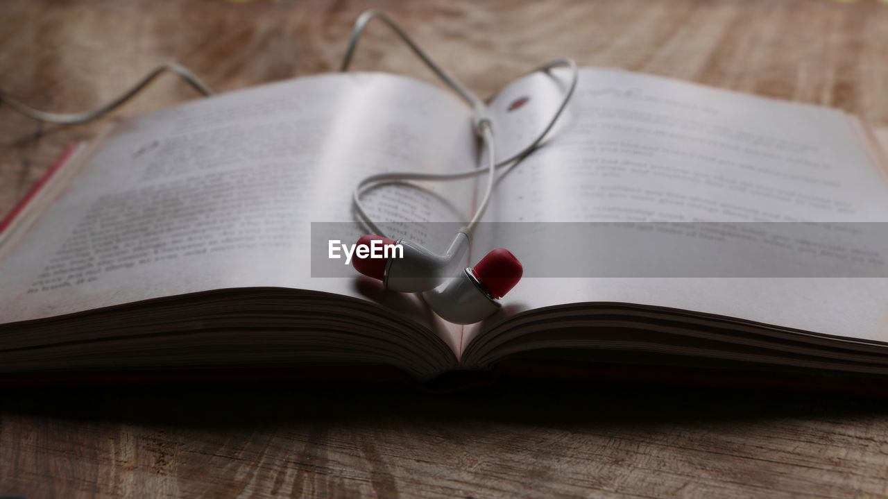Close-up of headphones in book on table