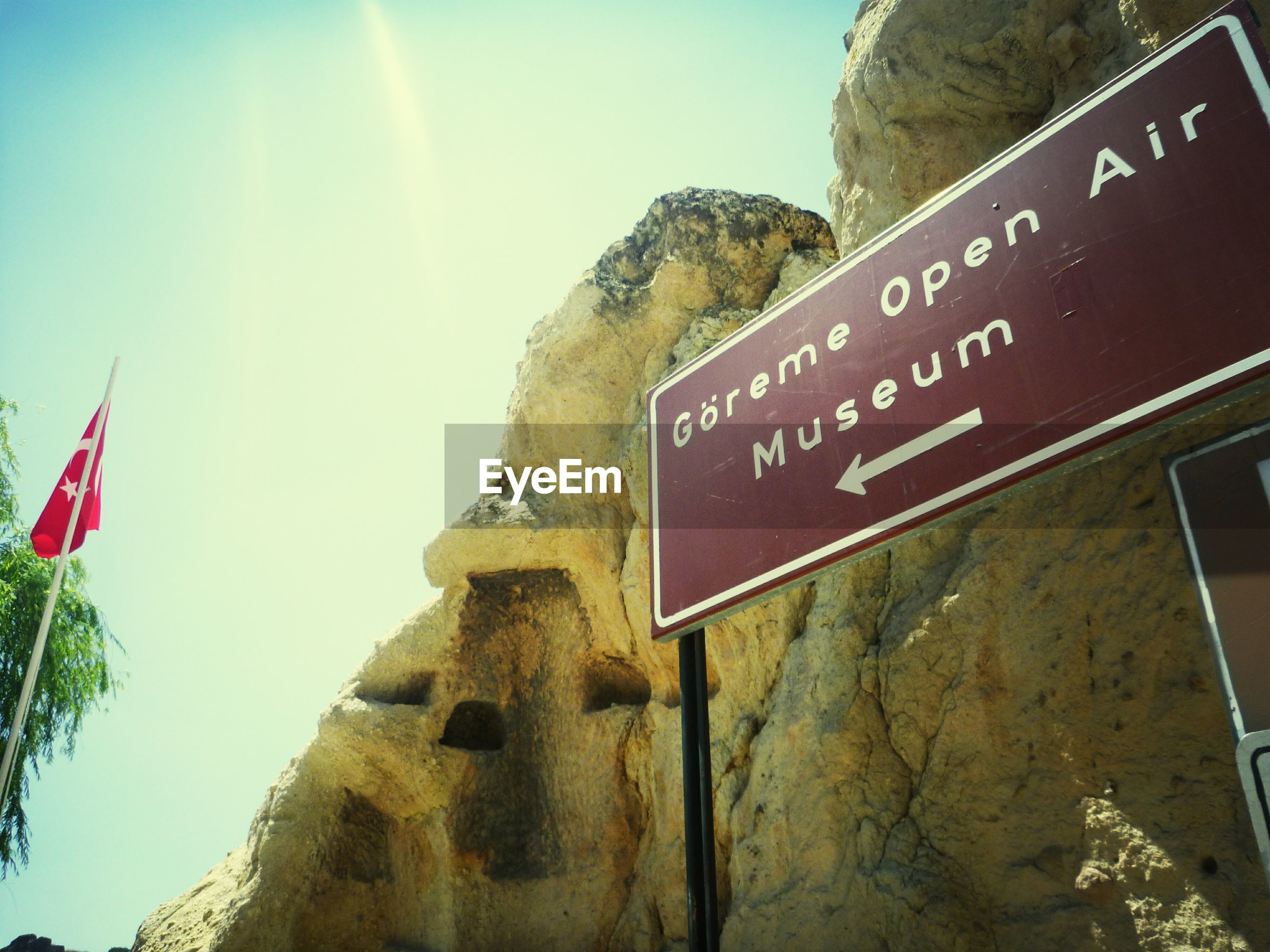 text, western script, communication, clear sky, guidance, low angle view, information sign, mountain, sunlight, sign, tree, road sign, sky, built structure, day, capital letter, blue, no people, non-western script, architecture