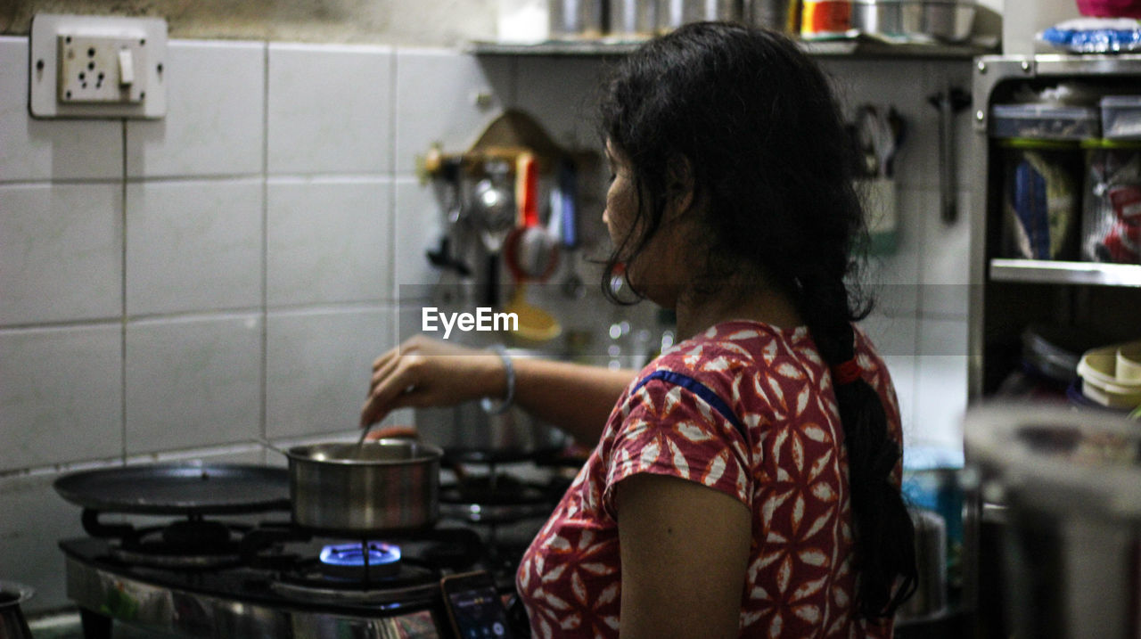 kitchen, domestic room, preparation, stove, indoors, domestic kitchen, home, women, kitchen utensil, household equipment, appliance, real people, lifestyles, rear view, one person, food and drink, standing, adult, casual clothing, preparing food, hairstyle