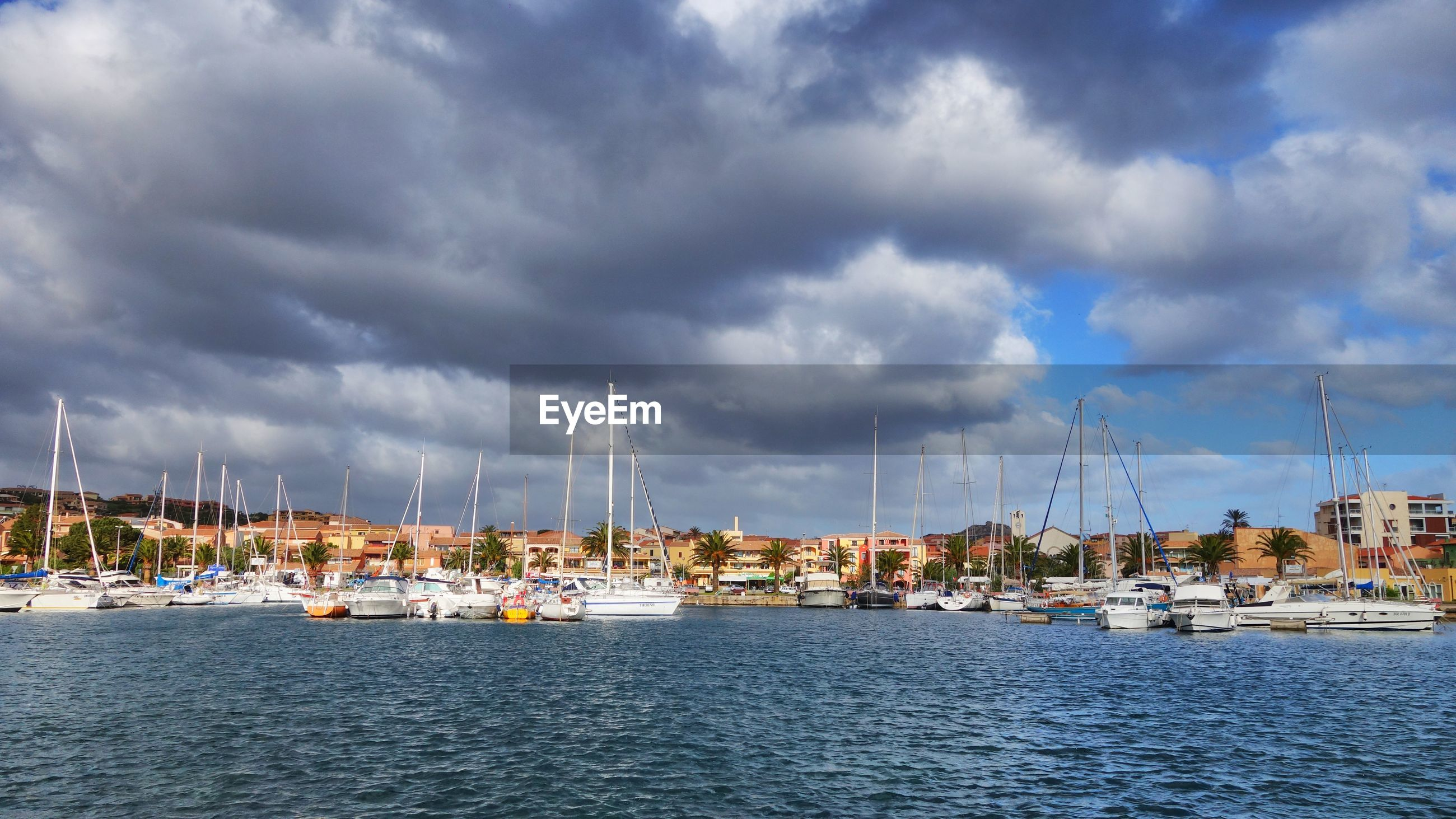 Boats moored at harbor in sea by city against cloudy sky