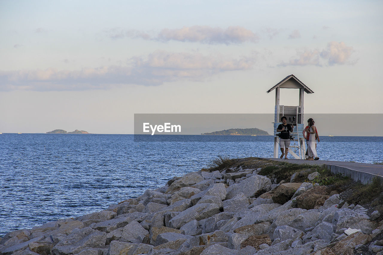 water, sea, sky, real people, men, lifestyles, cloud - sky, land, beauty in nature, horizon, beach, women, two people, leisure activity, people, adult, nature, rock, scenics - nature, horizon over water, outdoors, couple - relationship