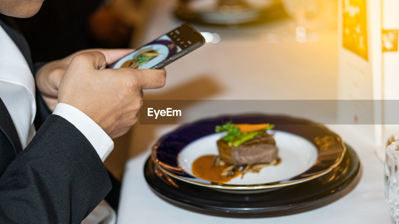 food and drink, indoors, food, holding, table, real people, men, one person, hand, close-up, focus on foreground, wireless technology, human hand, business, plate, mobile phone, technology, communication, freshness, meal