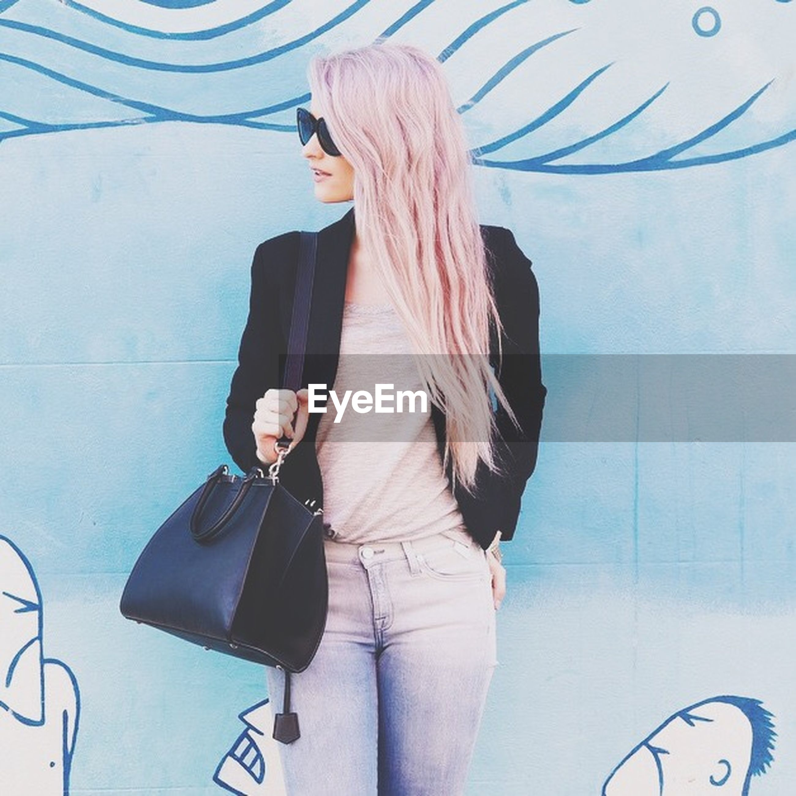 lifestyles, young adult, indoors, casual clothing, leisure activity, holding, communication, young women, wall - building feature, technology, standing, wireless technology, person, front view, three quarter length, fashion, photography themes, hobbies