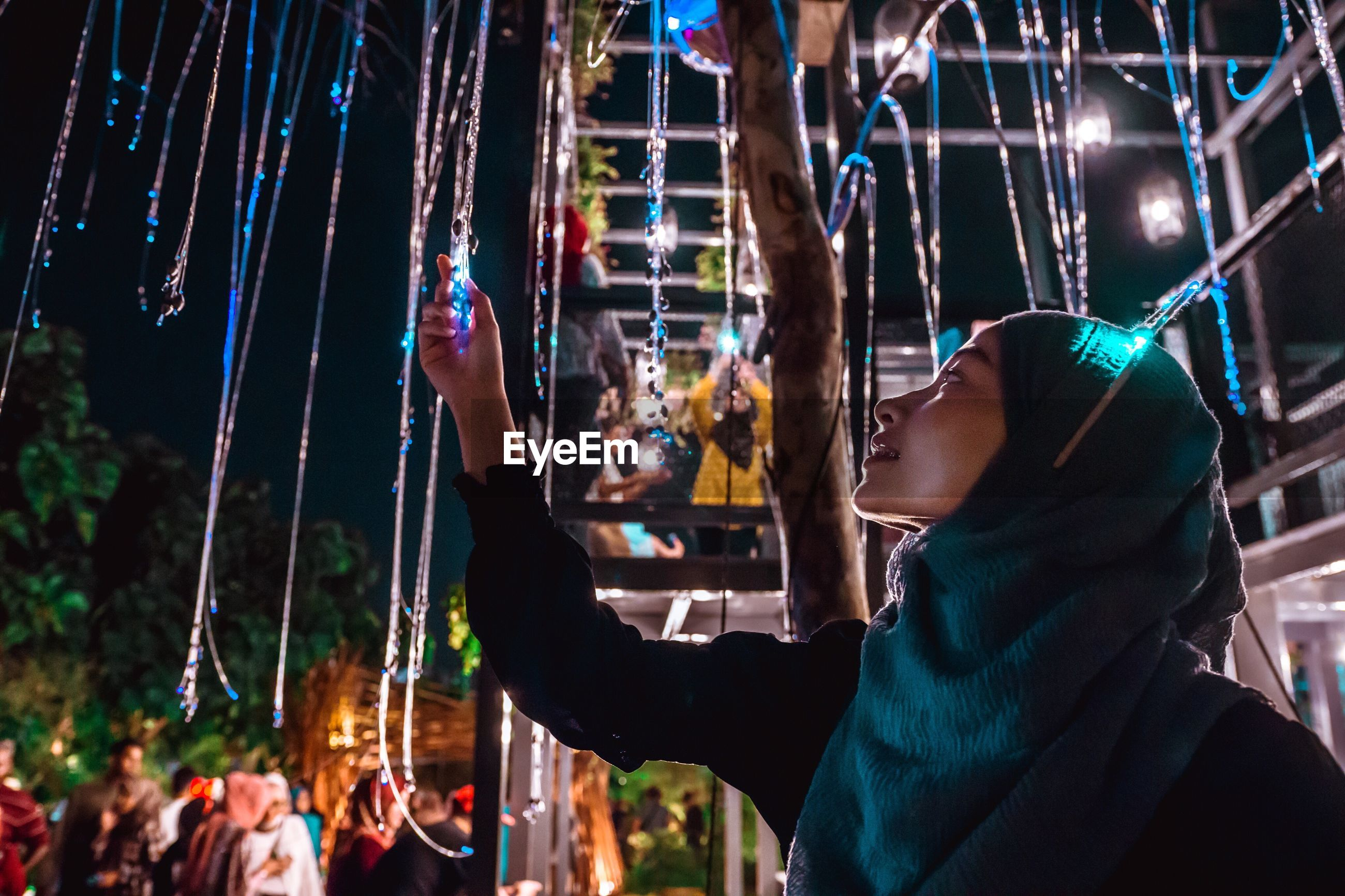 Young woman wearing hijab holding decoration at night