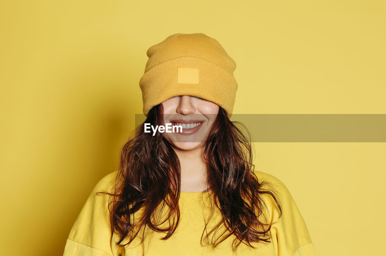 PORTRAIT OF SMILING WOMAN AGAINST YELLOW BACKGROUND