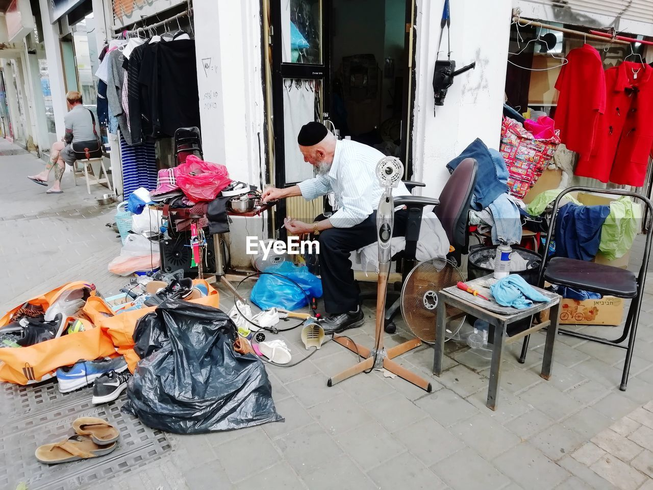 real people, occupation, working, men, one person, full length, architecture, day, adult, sitting, lifestyles, business, large group of objects, built structure, casual clothing, incidental people, equipment, messy, workshop