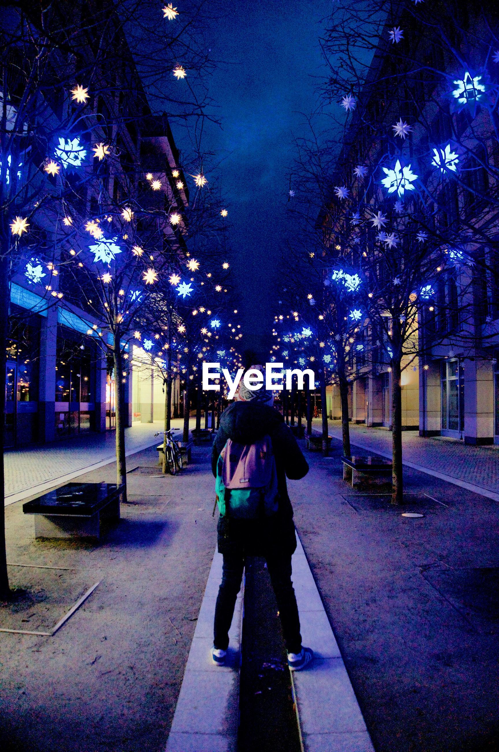 PEOPLE WALKING ON ILLUMINATED CHRISTMAS LIGHTS IN CITY