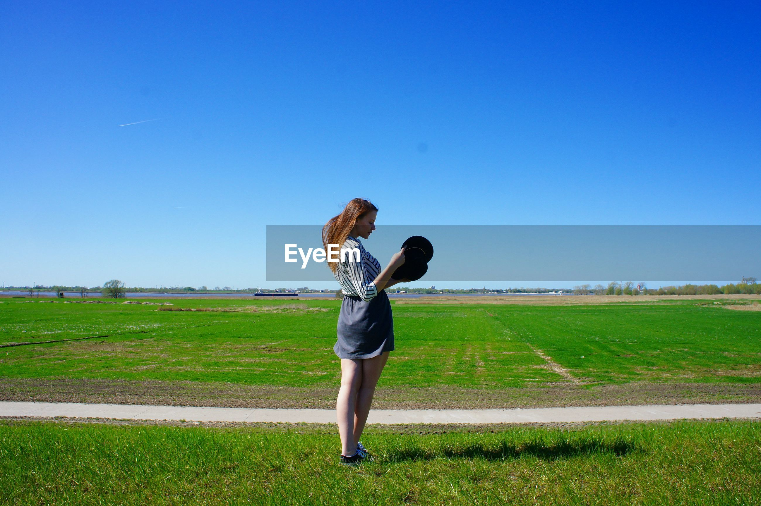 Full length of woman standing on field against clear blue sky