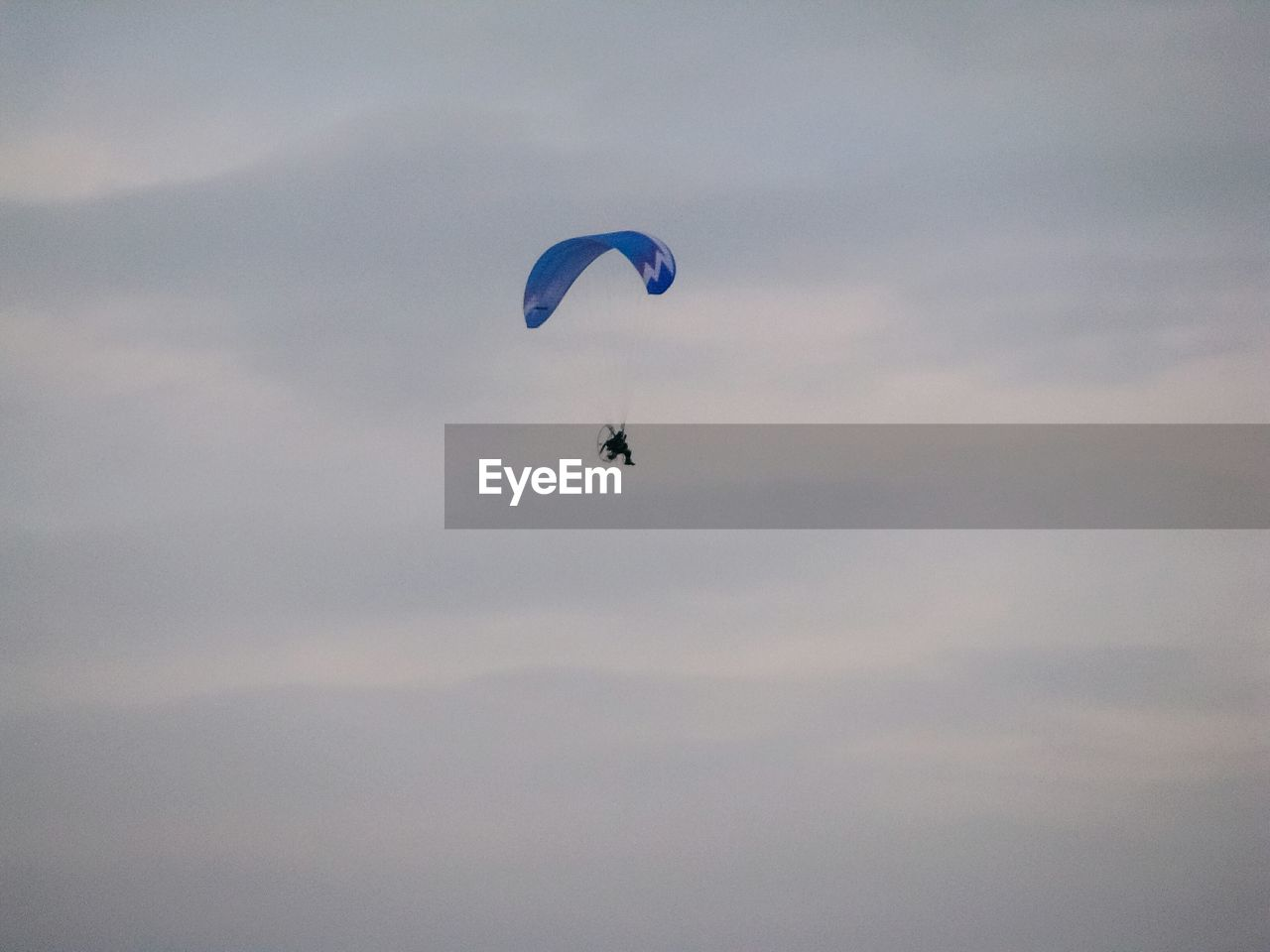 mid-air, extreme sports, parachute, low angle view, flying, adventure, outdoors, day, nature, sky, real people, one person, beauty in nature, paragliding