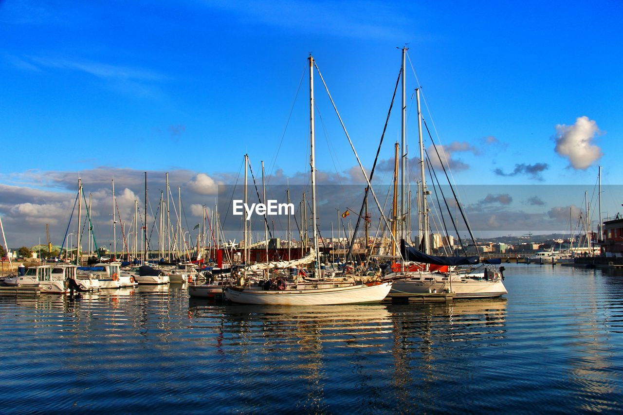 nautical vessel, moored, transportation, mode of transport, sky, water, mast, harbor, no people, reflection, sailboat, blue, waterfront, tranquility, day, outdoors, marina, nature, tranquil scene, scenics, sea, travel destinations, architecture, beauty in nature, yacht, mountain, building exterior