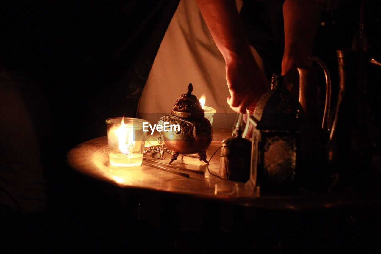 real people, indoors, one person, human hand, heat - temperature, human body part, night, drink, food and drink, midsection, drinking glass, preparation, flame, human leg, holding, illuminated, men, low section, close-up, freshness, people