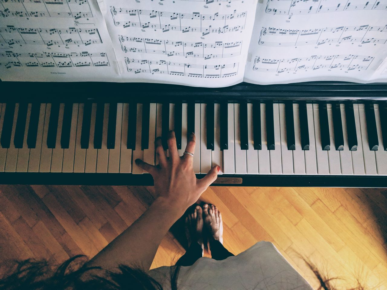 Low Section Of Woman Playing Piano At Home