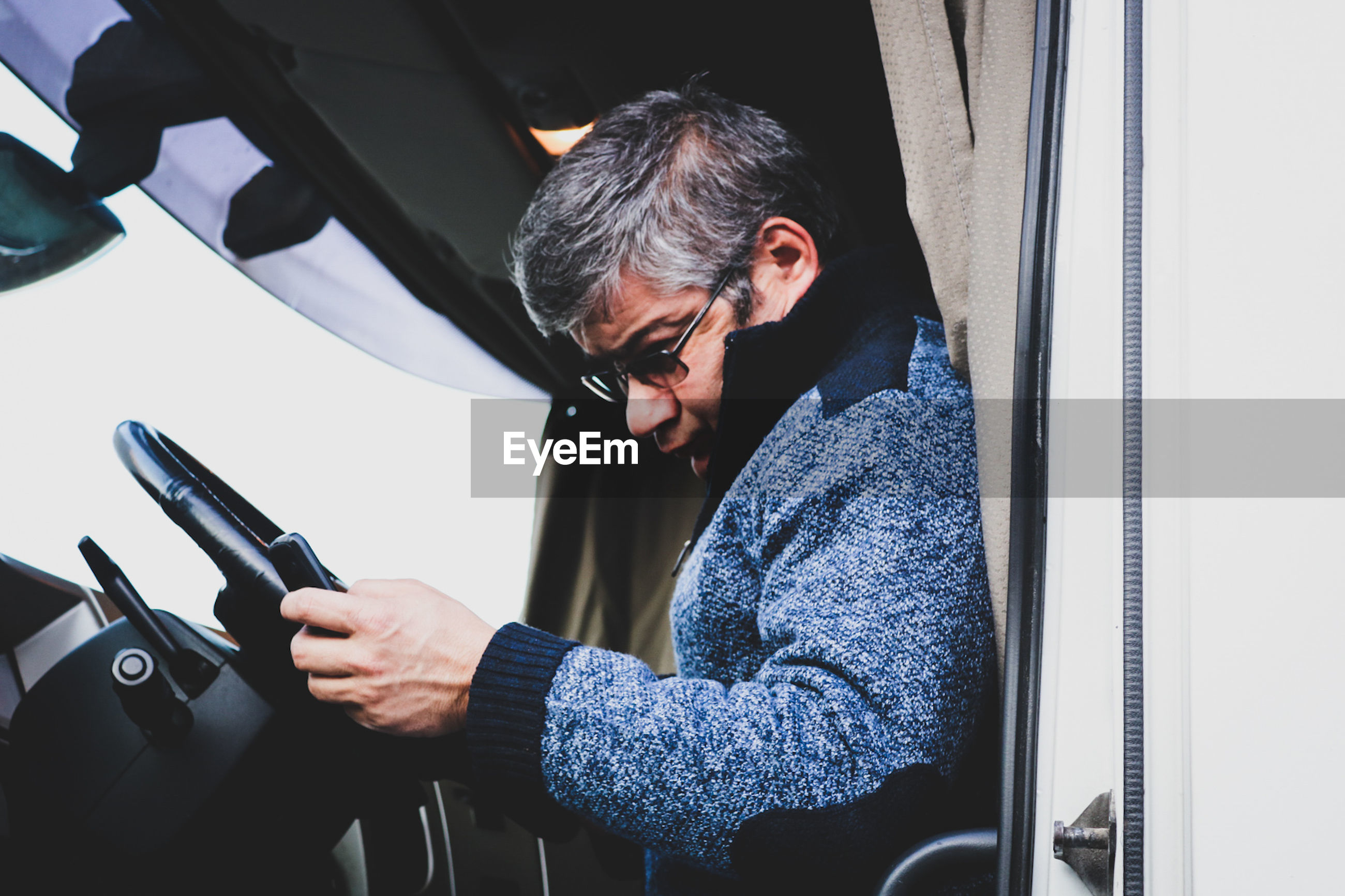 Side view of man sitting in vehicle