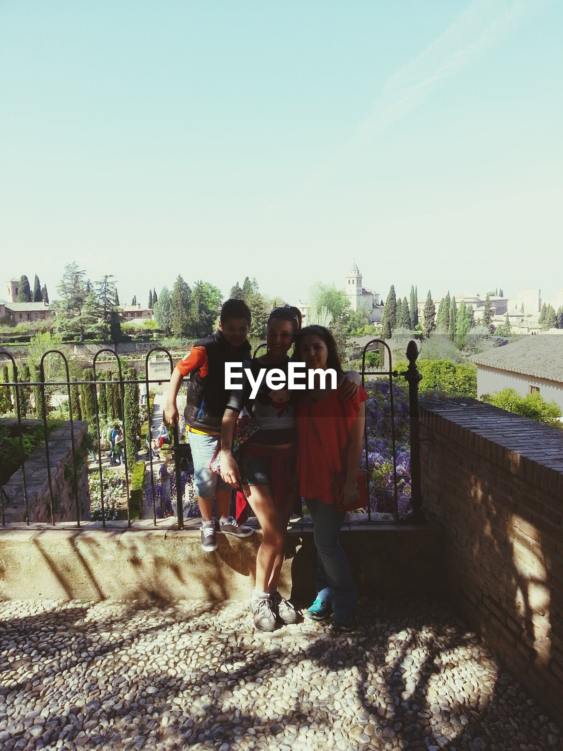 clear sky, lifestyles, togetherness, leisure activity, men, full length, bonding, rear view, casual clothing, love, person, boys, railing, copy space, childhood, friendship, girls, built structure