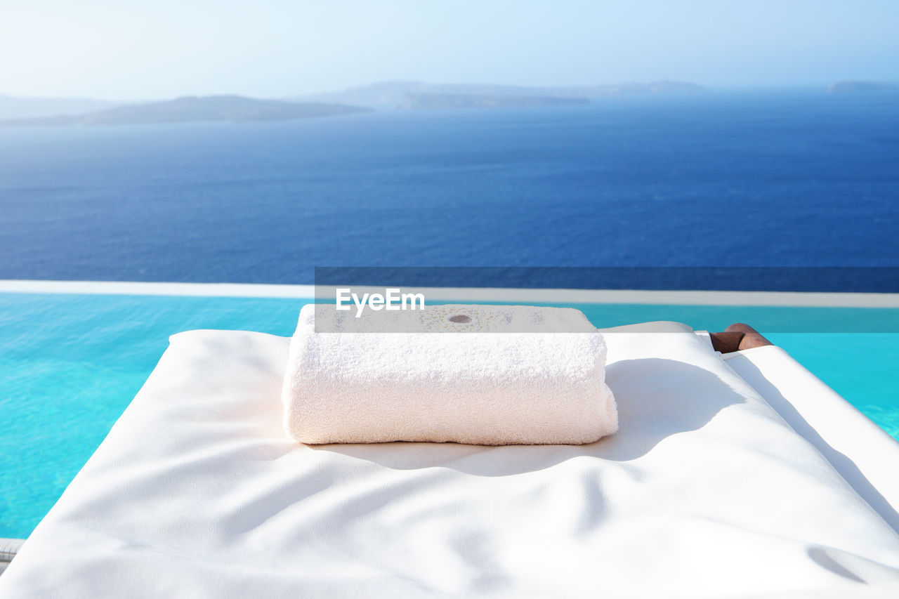Close-Up Of Towel On Lounge Chair At Infinity Pool Against Sea