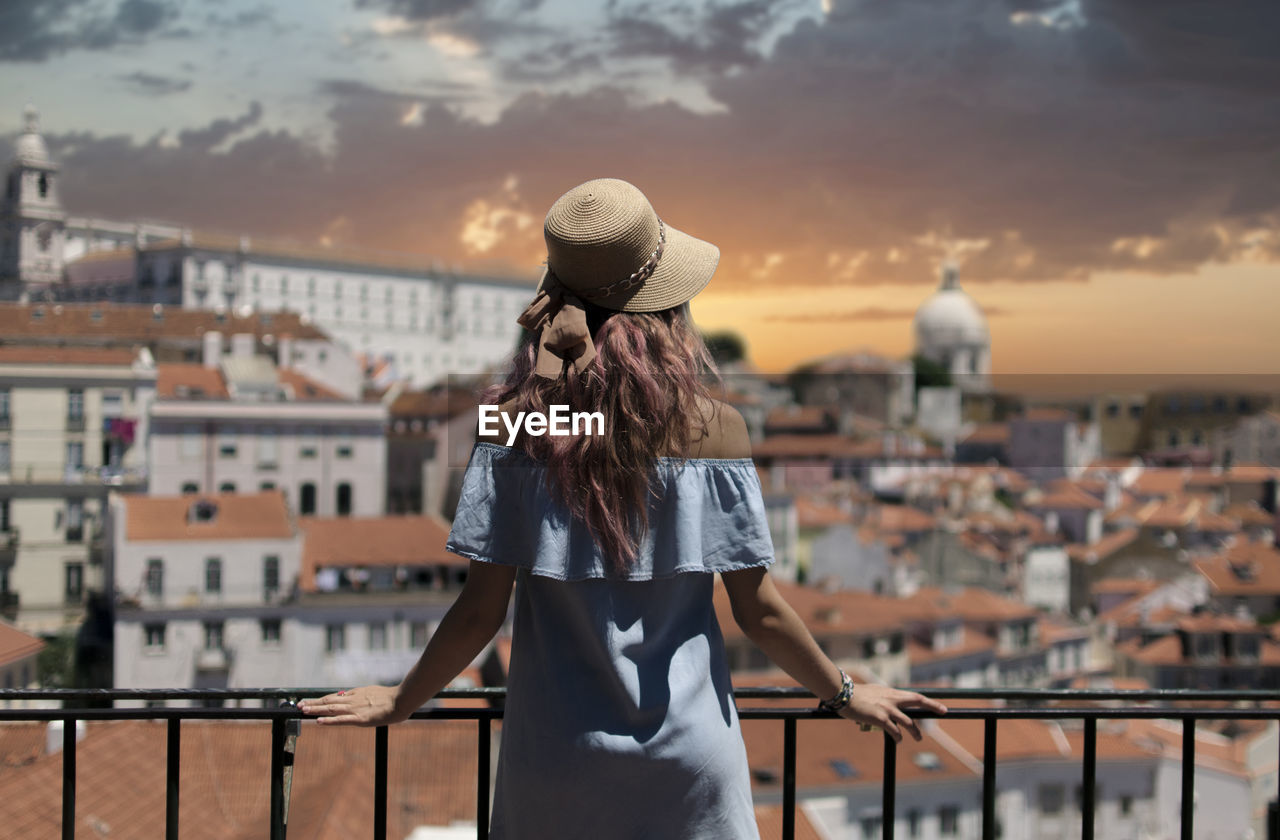 Rear View Of Young Woman Looking At Cityscape While Standing By Railing In Balcony Against Sky During Sunset