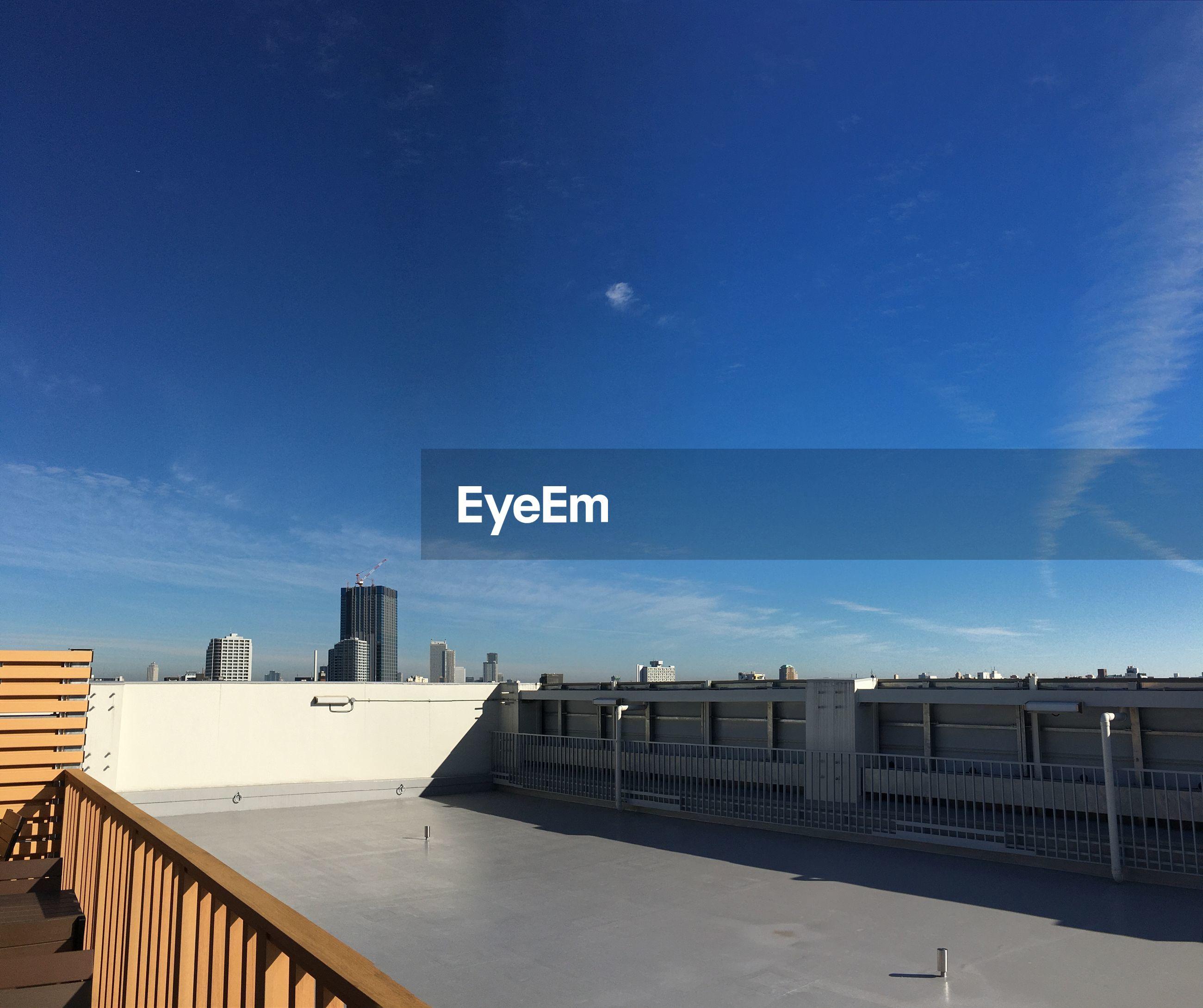 Building terrace in city against blue sky