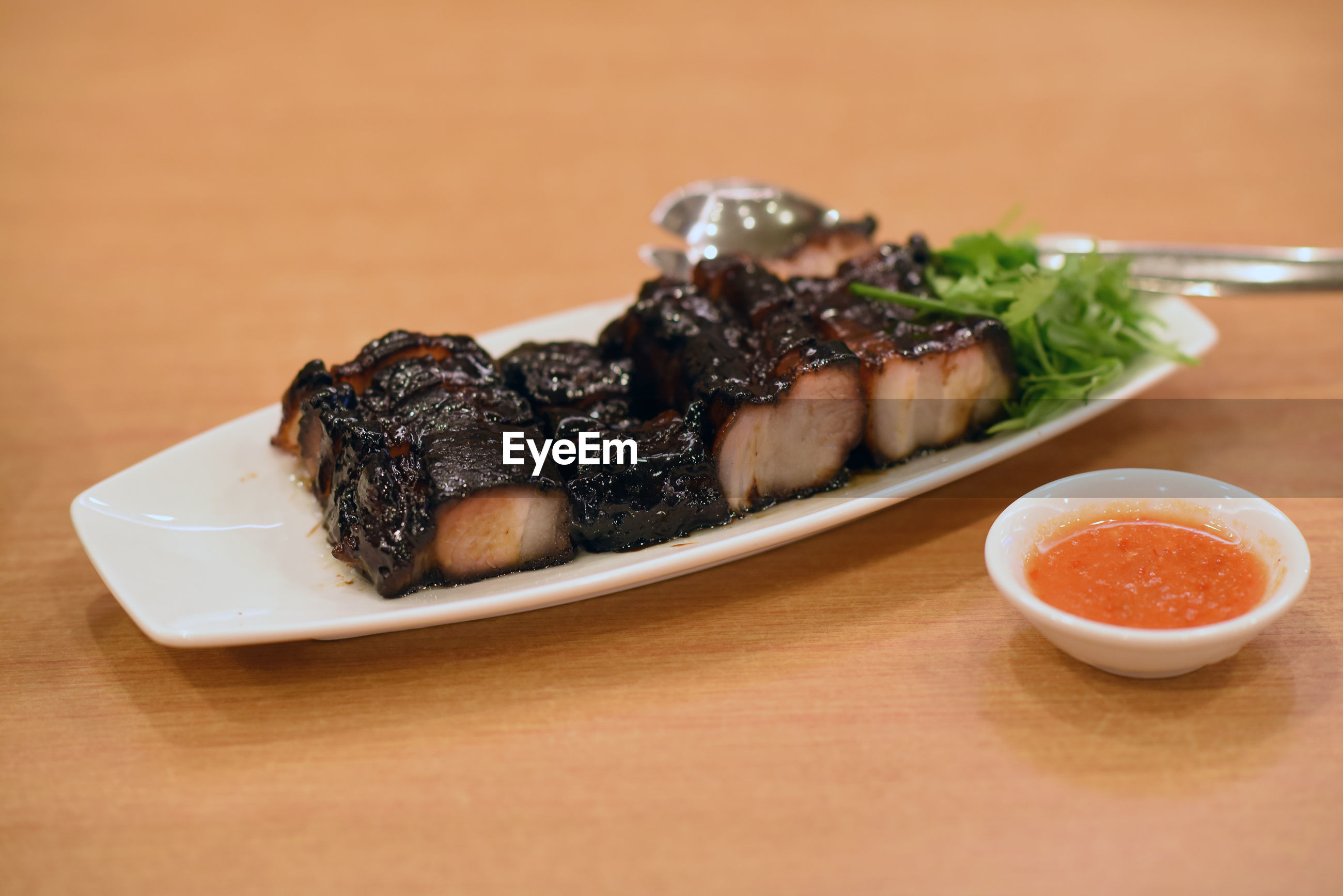 Close-up of roasted pork belly served on wooden table