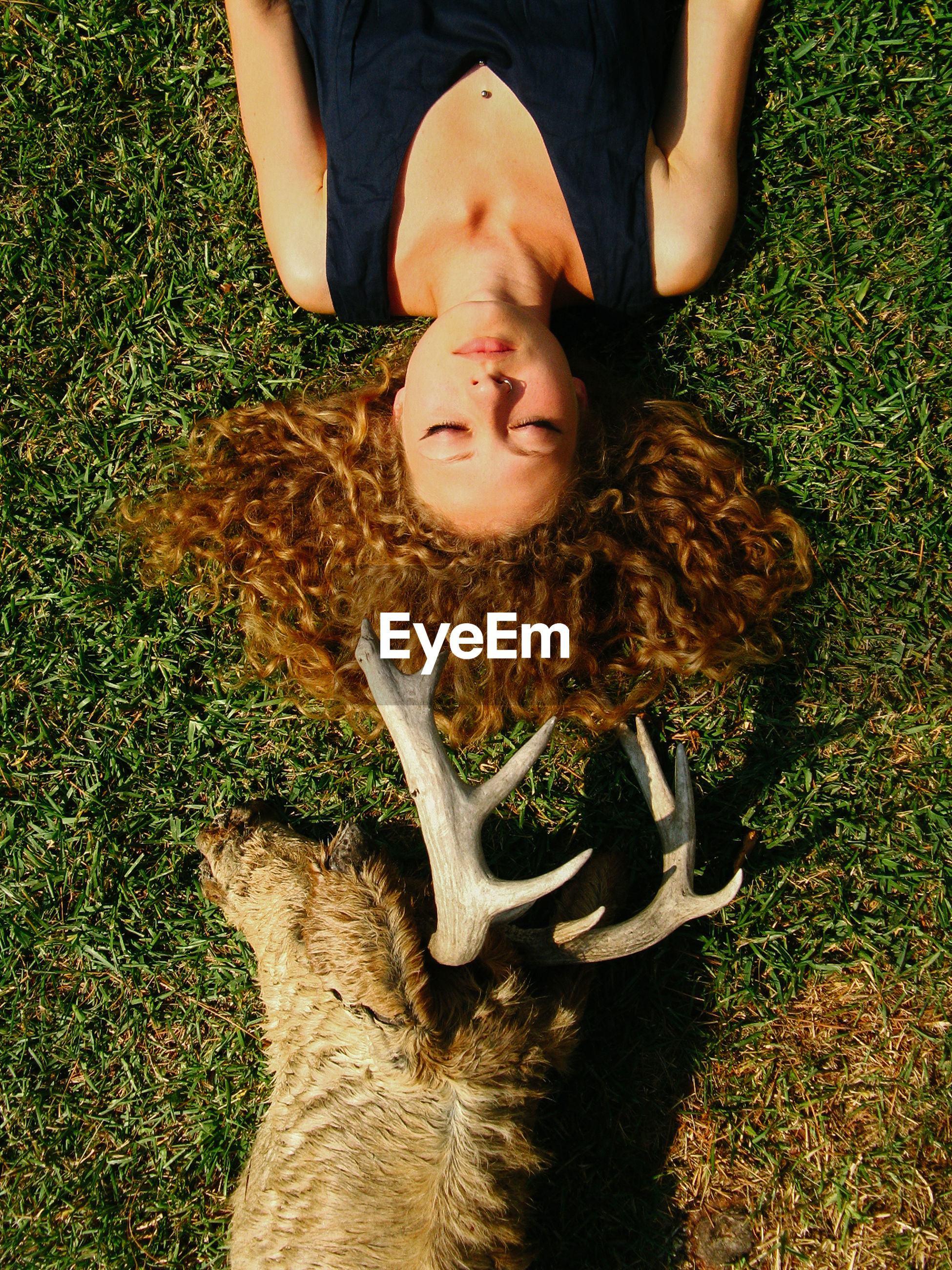 lying down, one person, high angle view, real people, leisure activity, lying on back, lifestyles, grass, relaxation, casual clothing, plant, nature, land, front view, young adult, field, eyes closed, hairstyle, outdoors