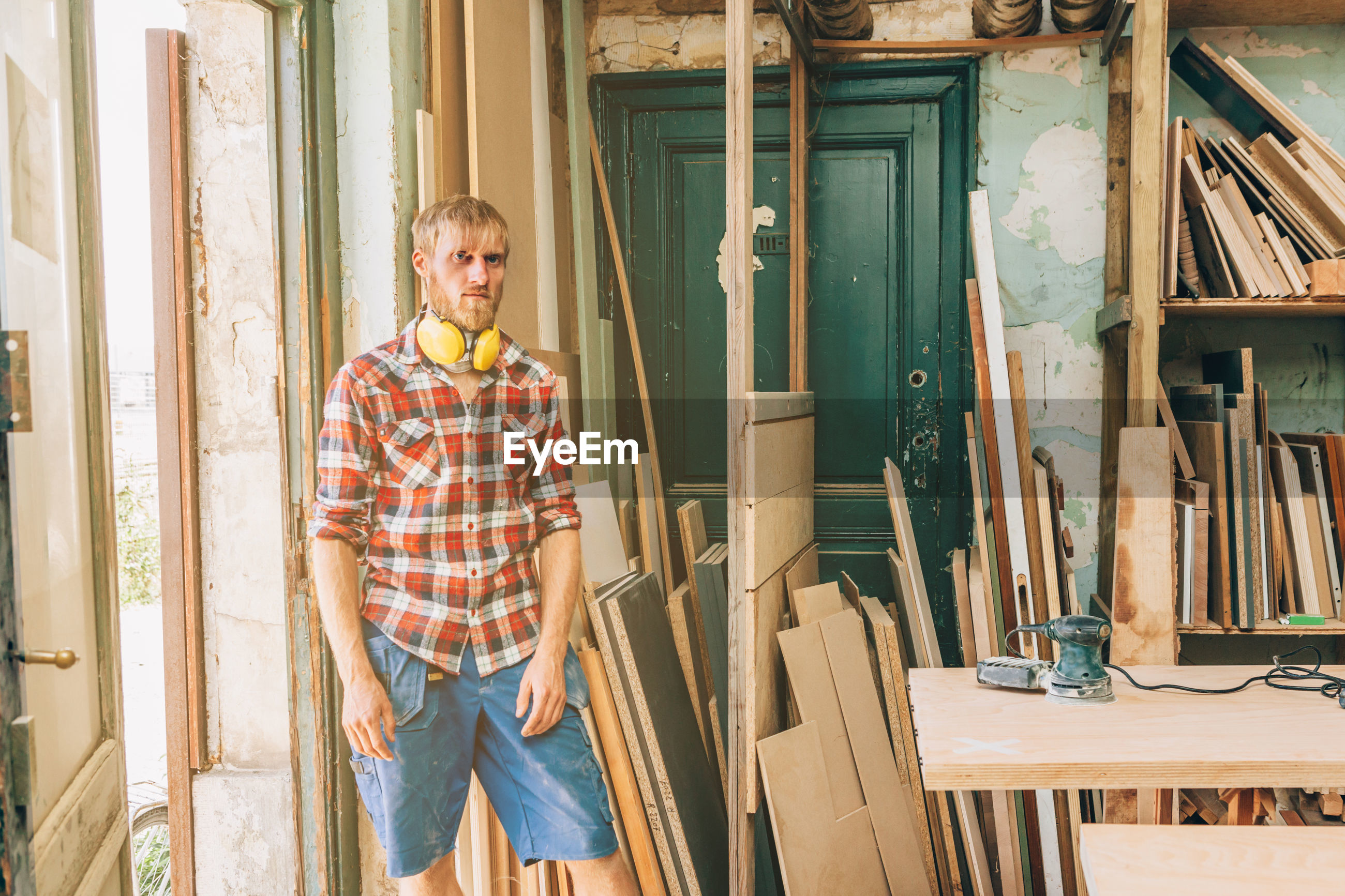 Portrait of man standing by table at workshop