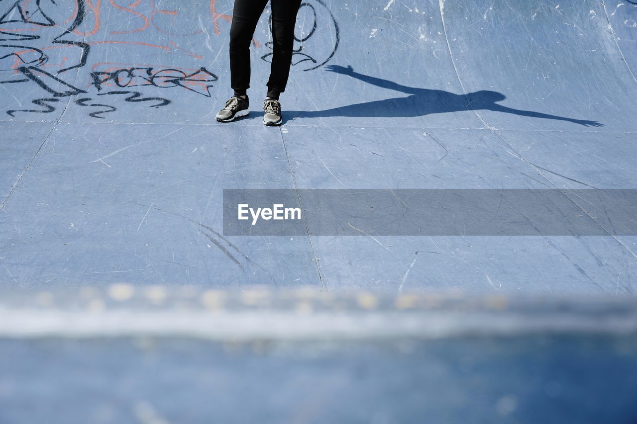 Low Section Of Man Standing At Skateboard Park