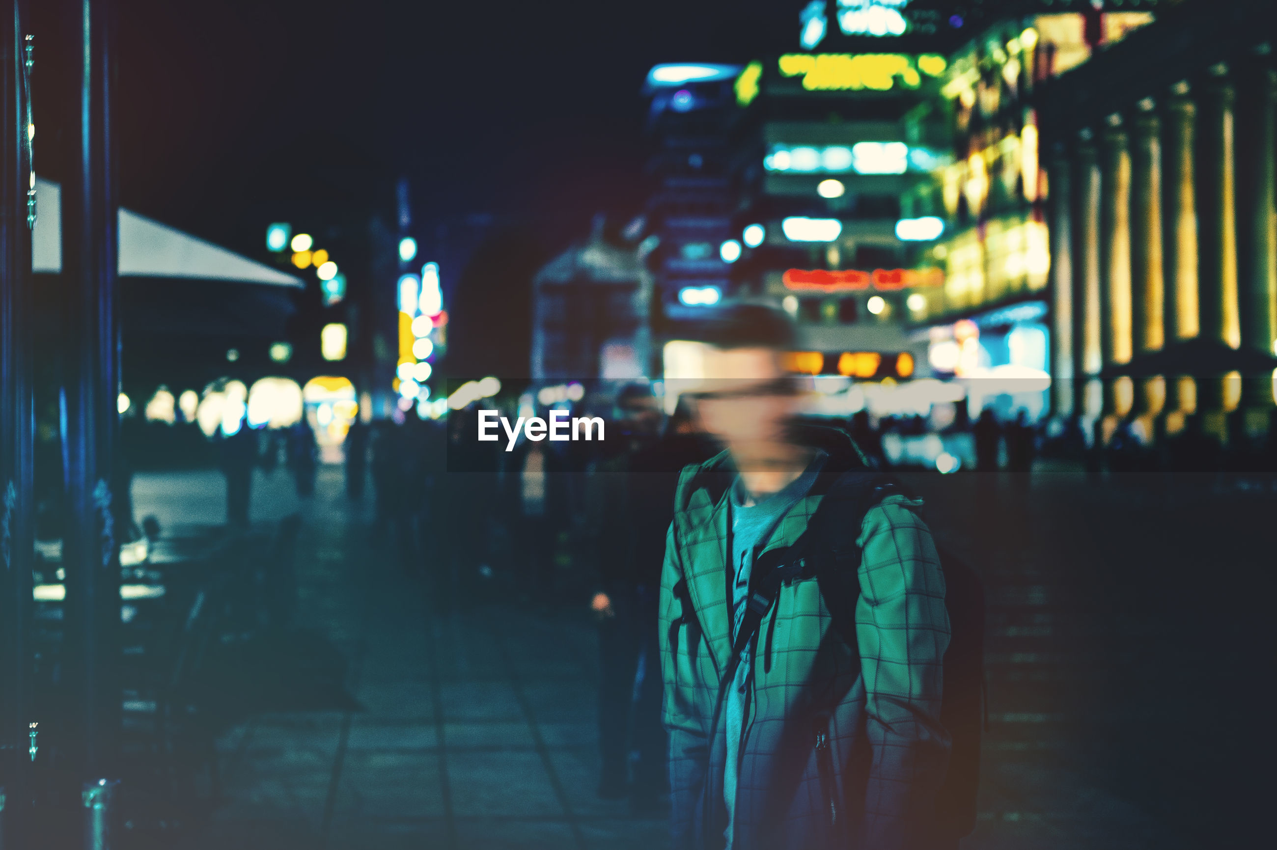 Blurred motion of man on street in city at night