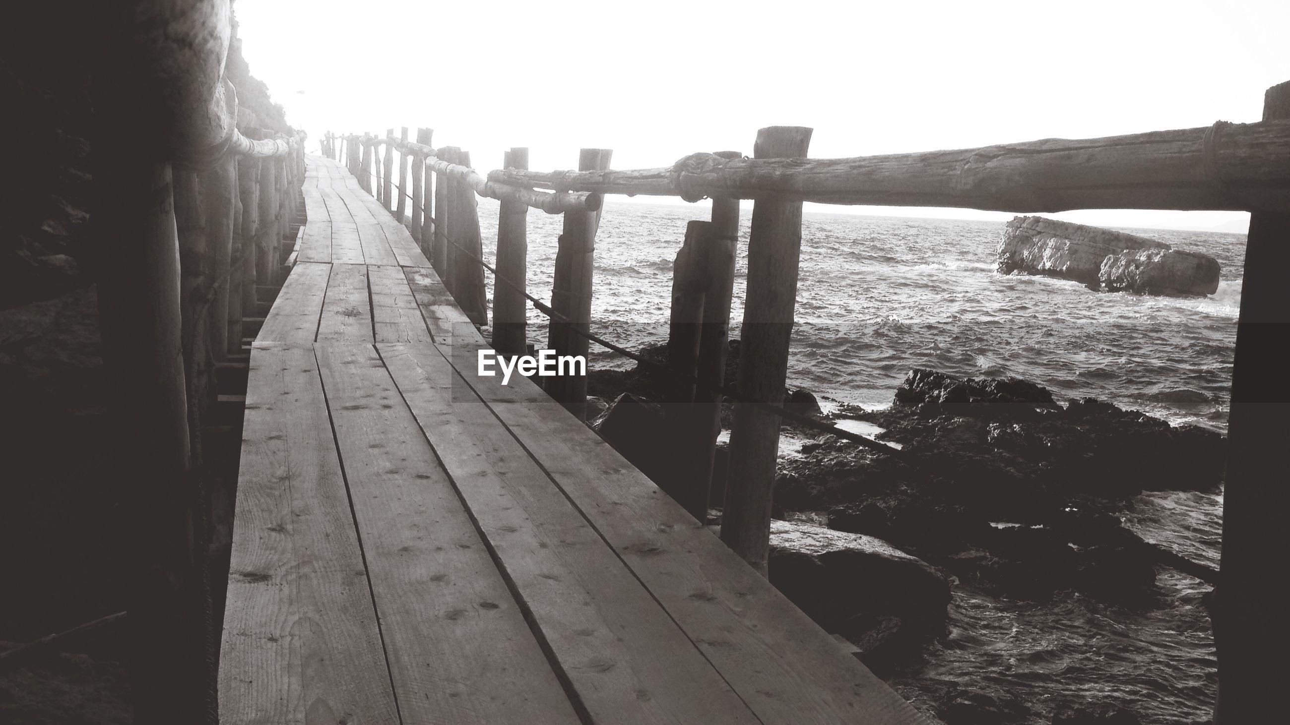 Footbridge by sea against sky