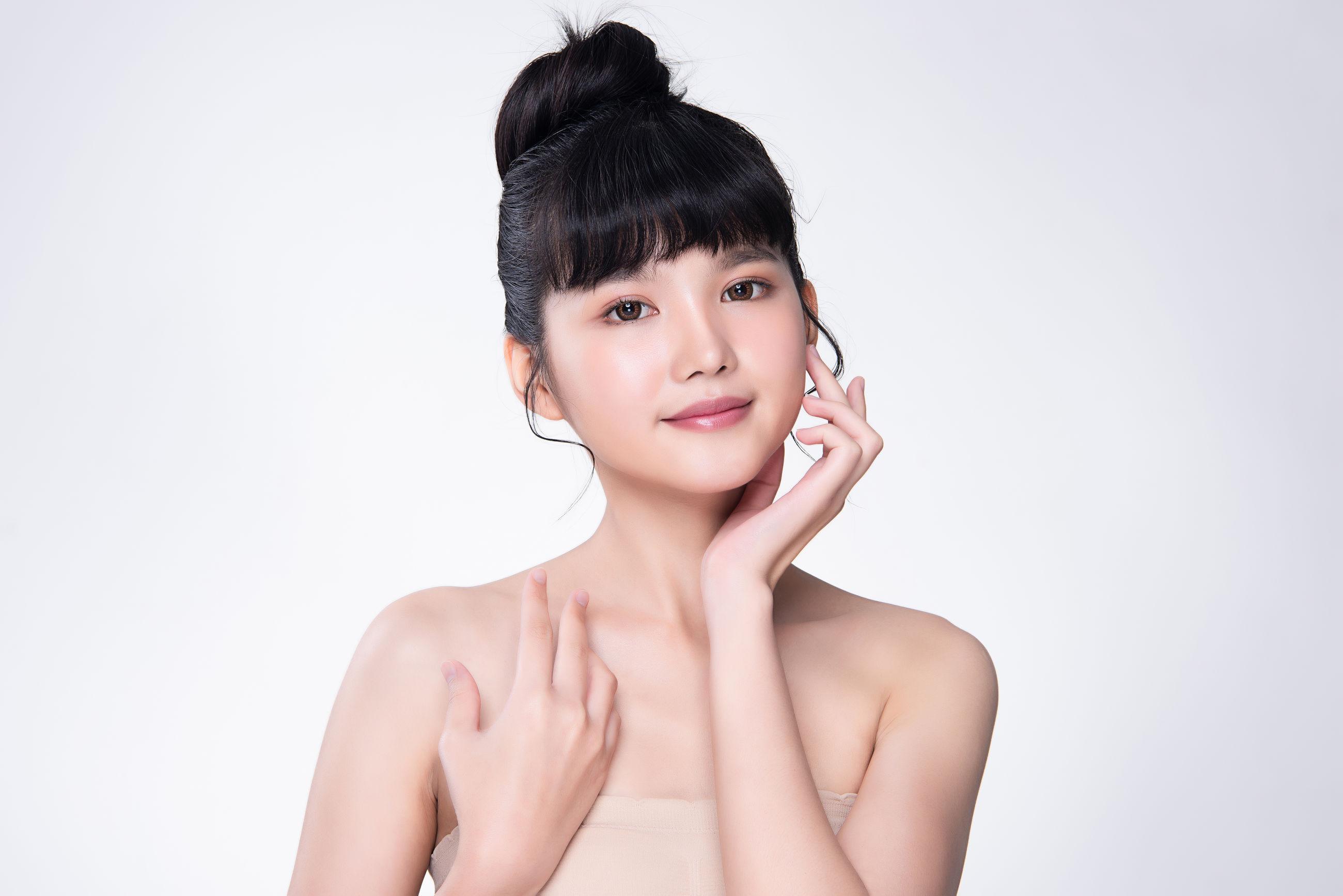 Portrait of confident beautiful woman against white background