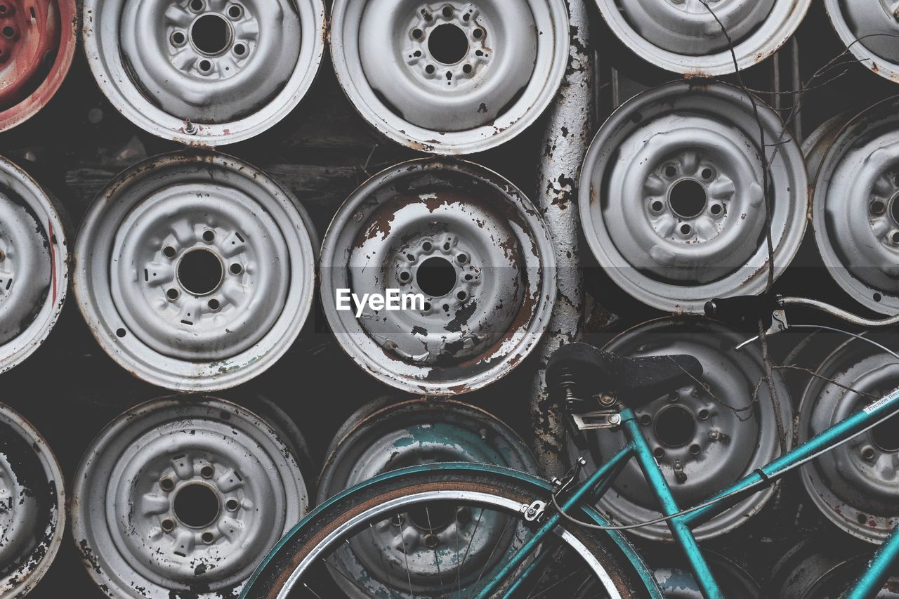 Bicycle parked against wheel rims on wall