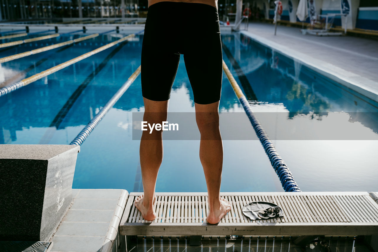 LOW SECTION OF MAN STANDING AT SWIMMING POOL