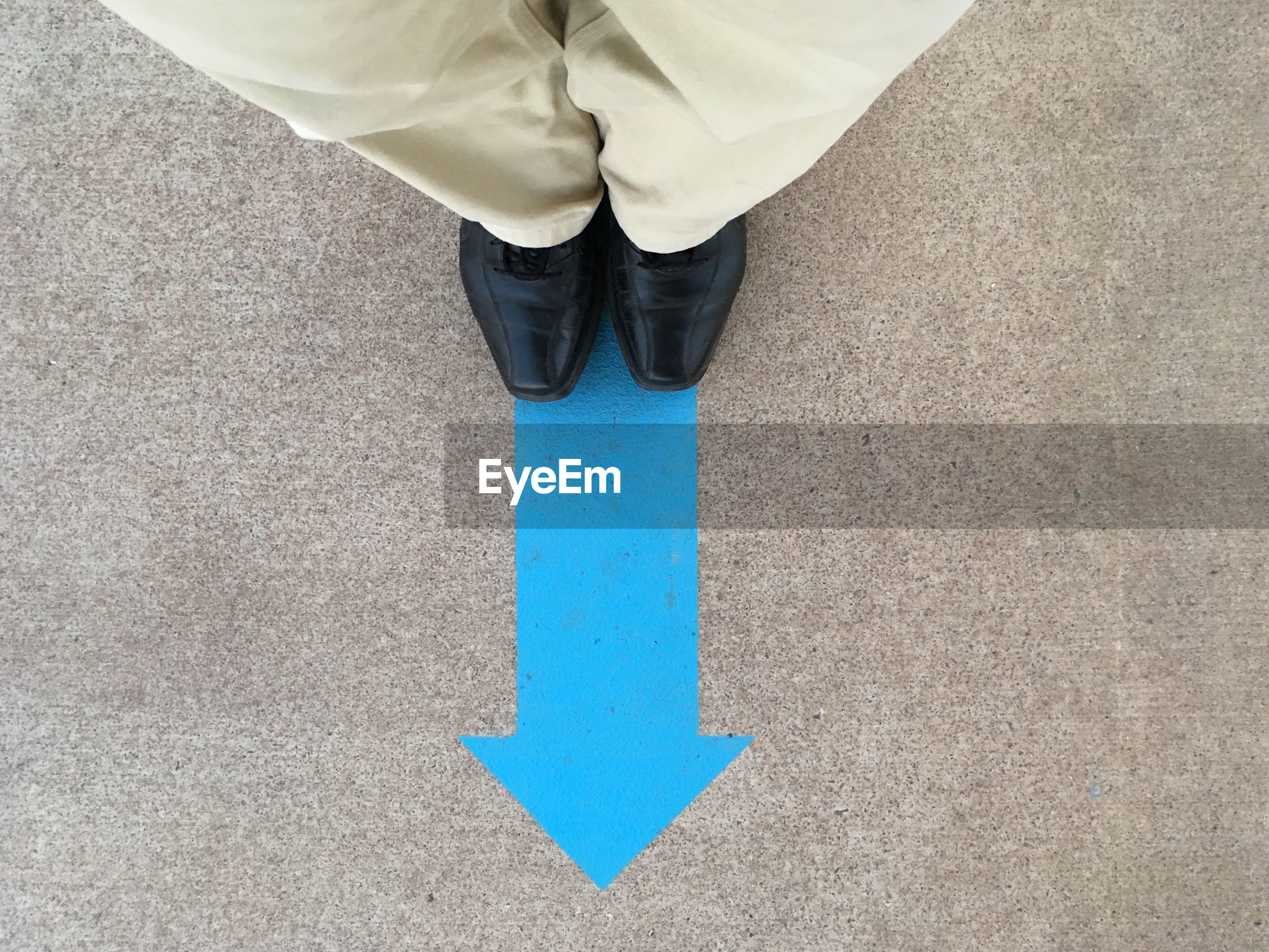 Low section of man standing on blue arrow symbol