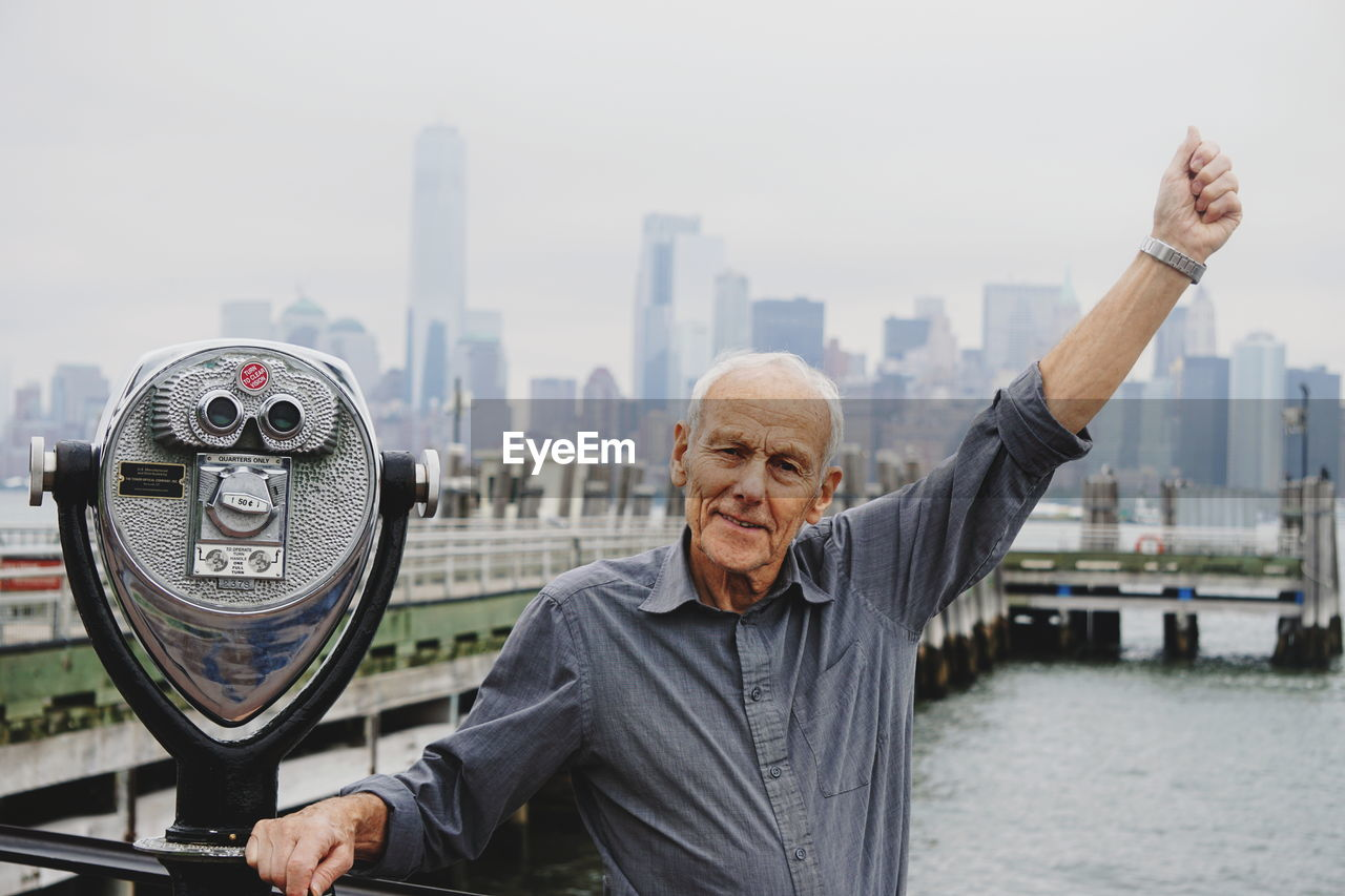 Portrait of senior man standing by coin-operated binoculars against river in city