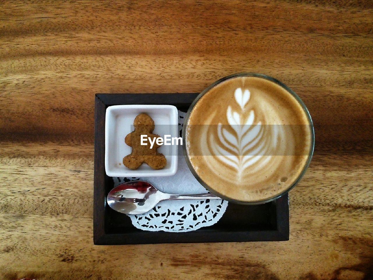 Directly Above Shot Of Coffee And Gingerbread Man In Tray On Wooden Table
