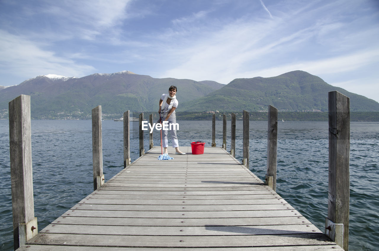 Woman Cleaning Pier Over Lake Against Mountains