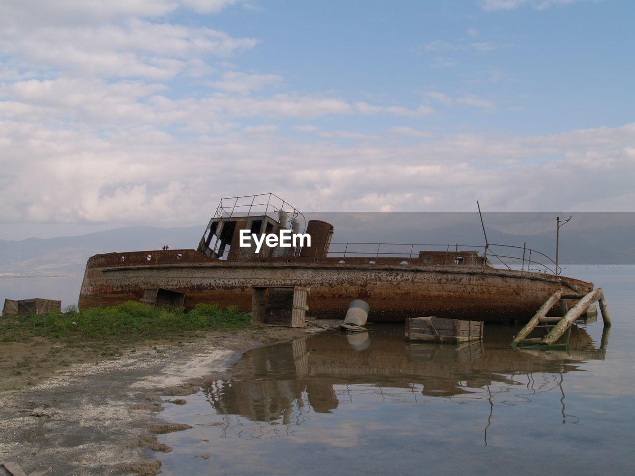 ABANDONED BOAT AT LAKE AGAINST SKY