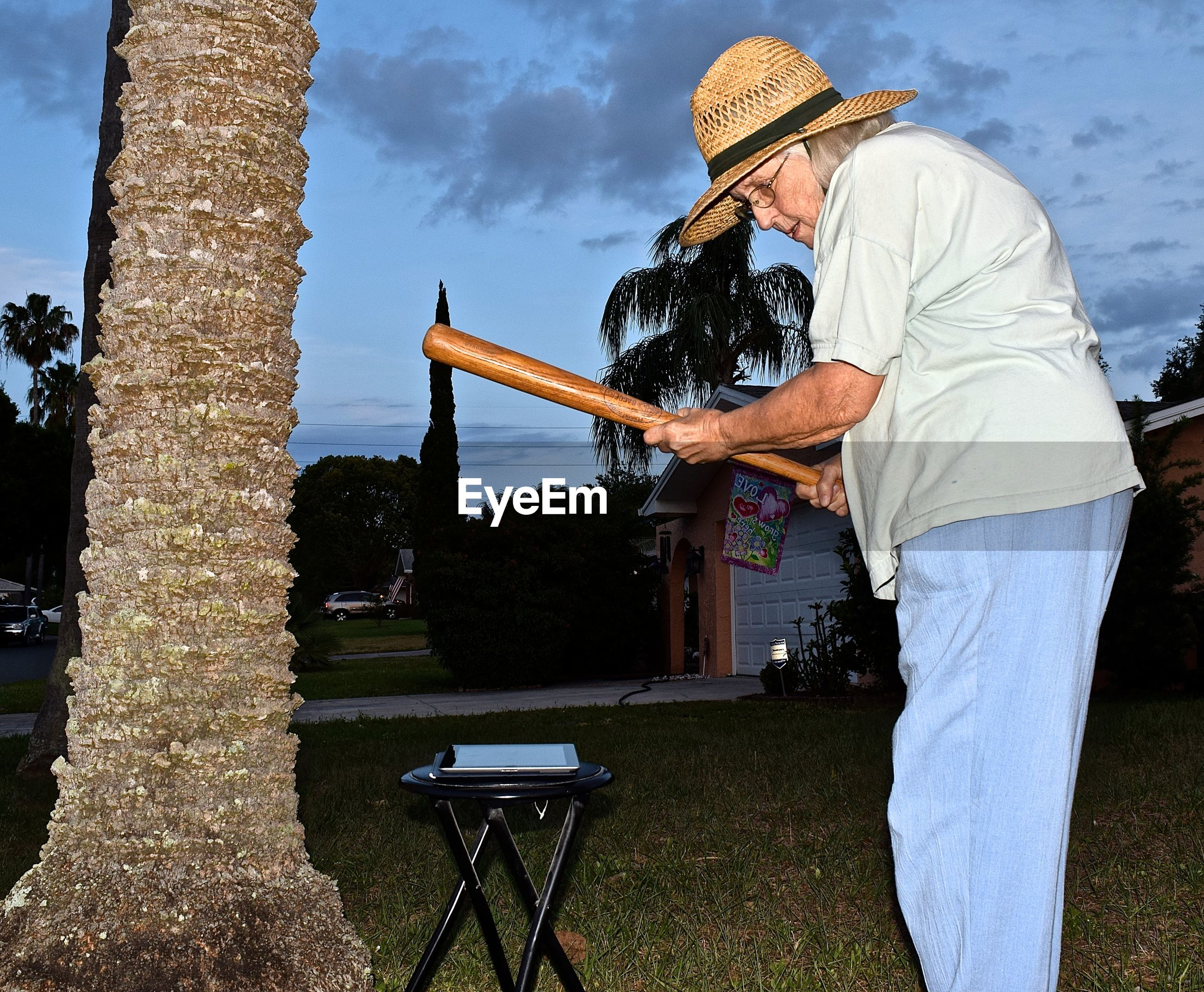 Woman with baseball bat looking at digital tablet on stool in yard at dusk