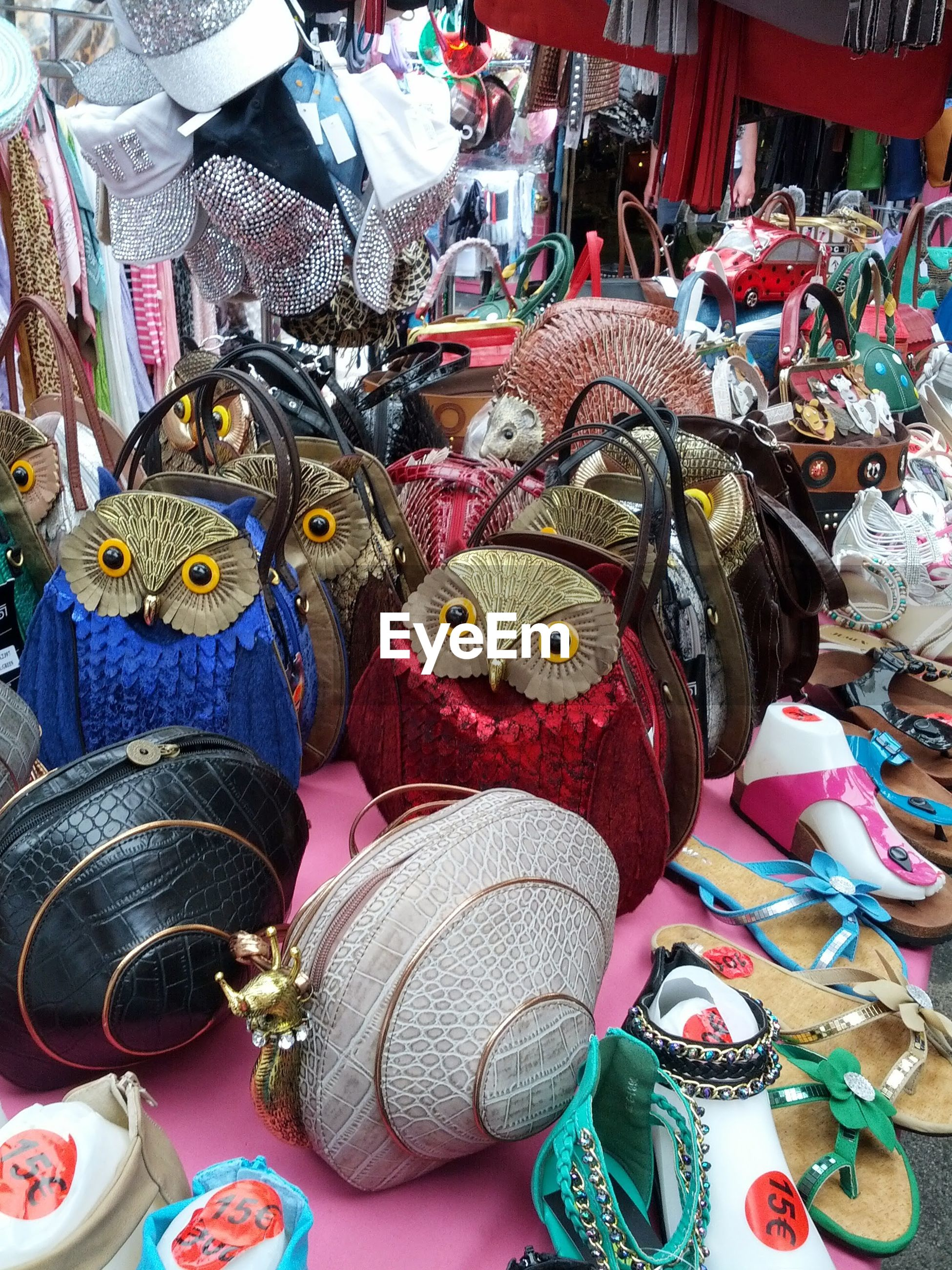 High angle view of hand bags with sandals on market stall for sale