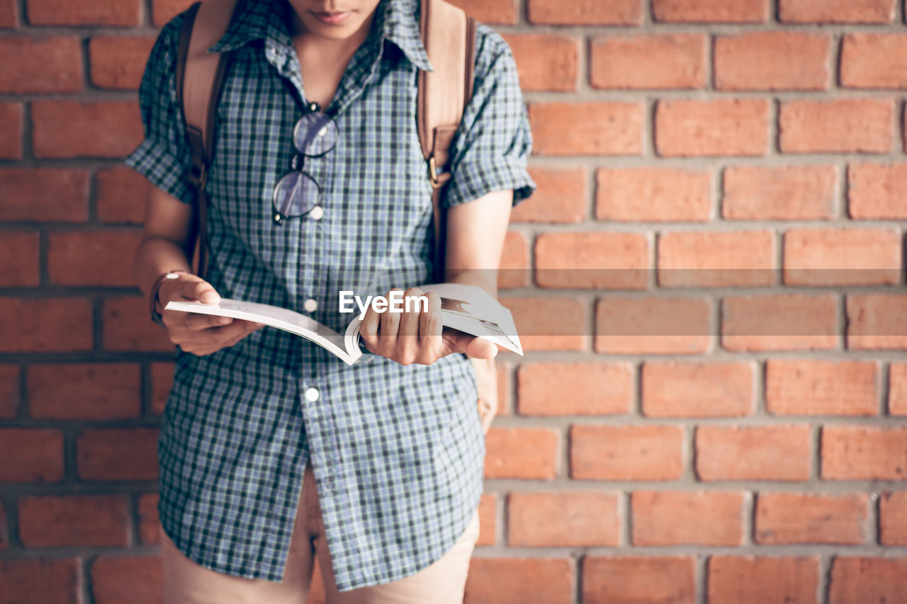 Midsection of woman holding book while standing against brick wall