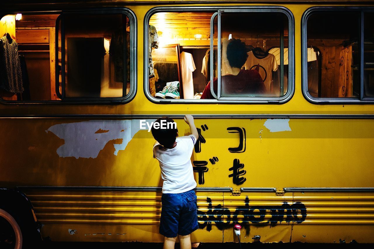 Rear view of boy standing in front of yellow bus