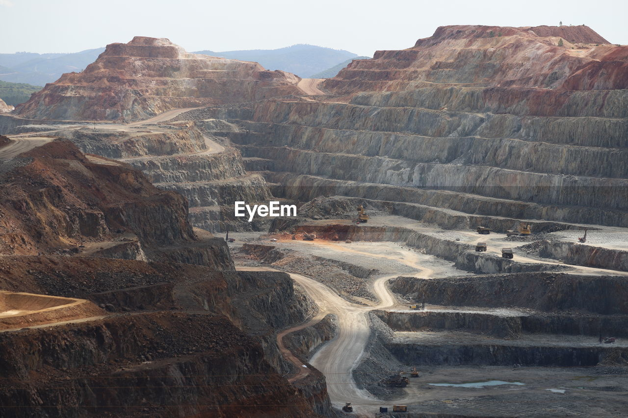 Aerial view of open cast mine with mountain range in background