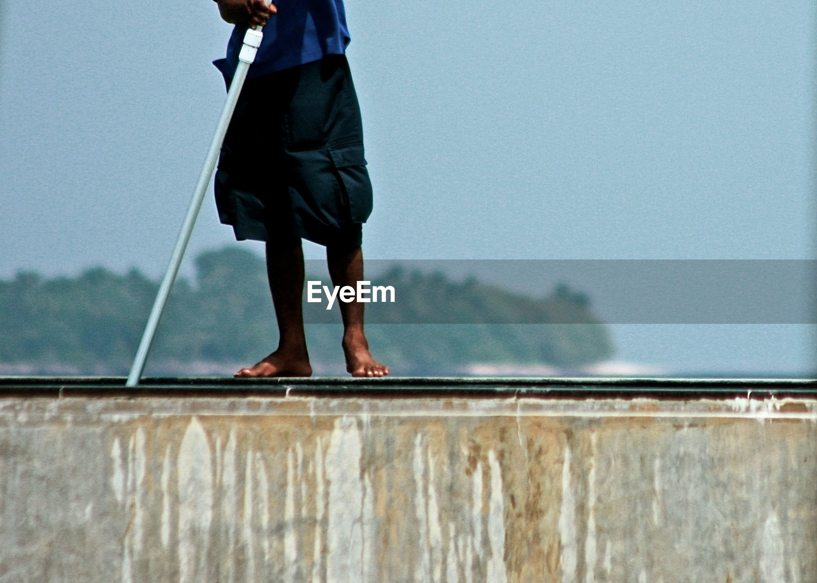 Low section of worker cleaning infinity pool against sky