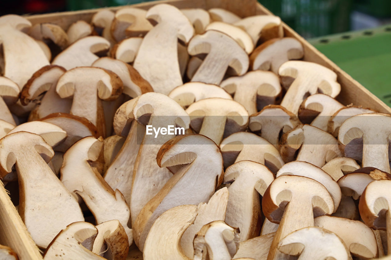 Close-Up Of Halved Porcini Mushrooms In Wooden Box