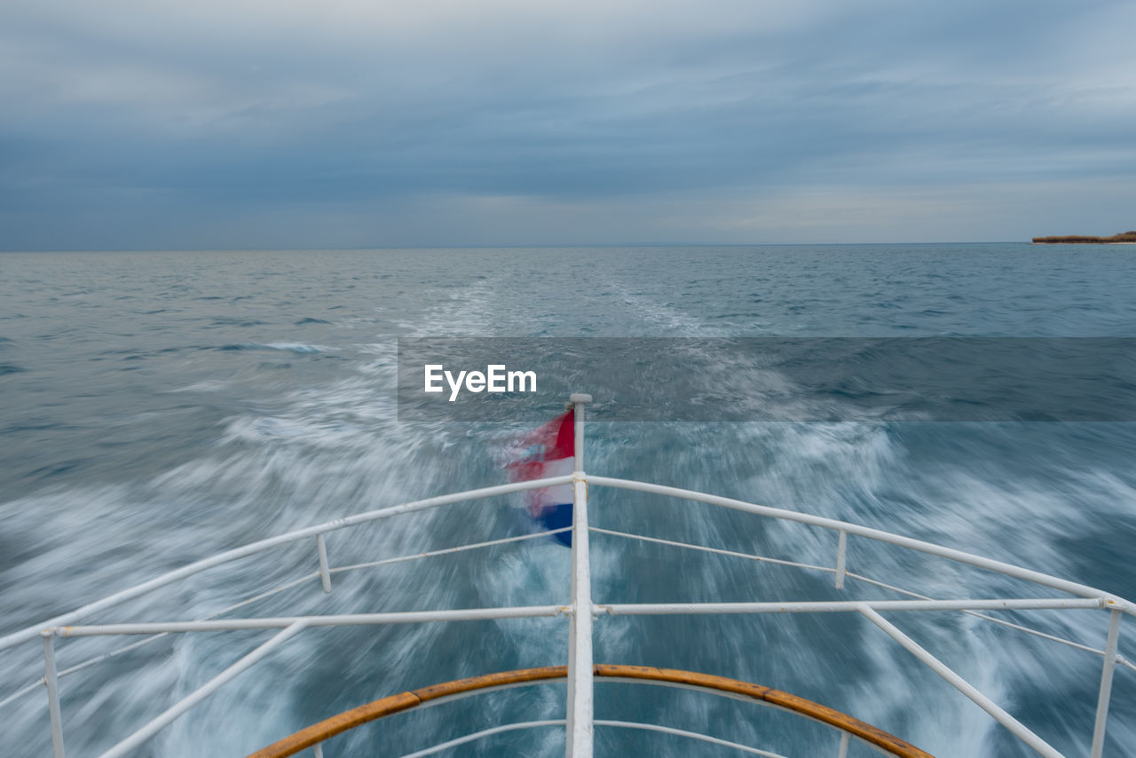 Cropped Image Of Boat Sailing On Sea Against Cloudy Sky