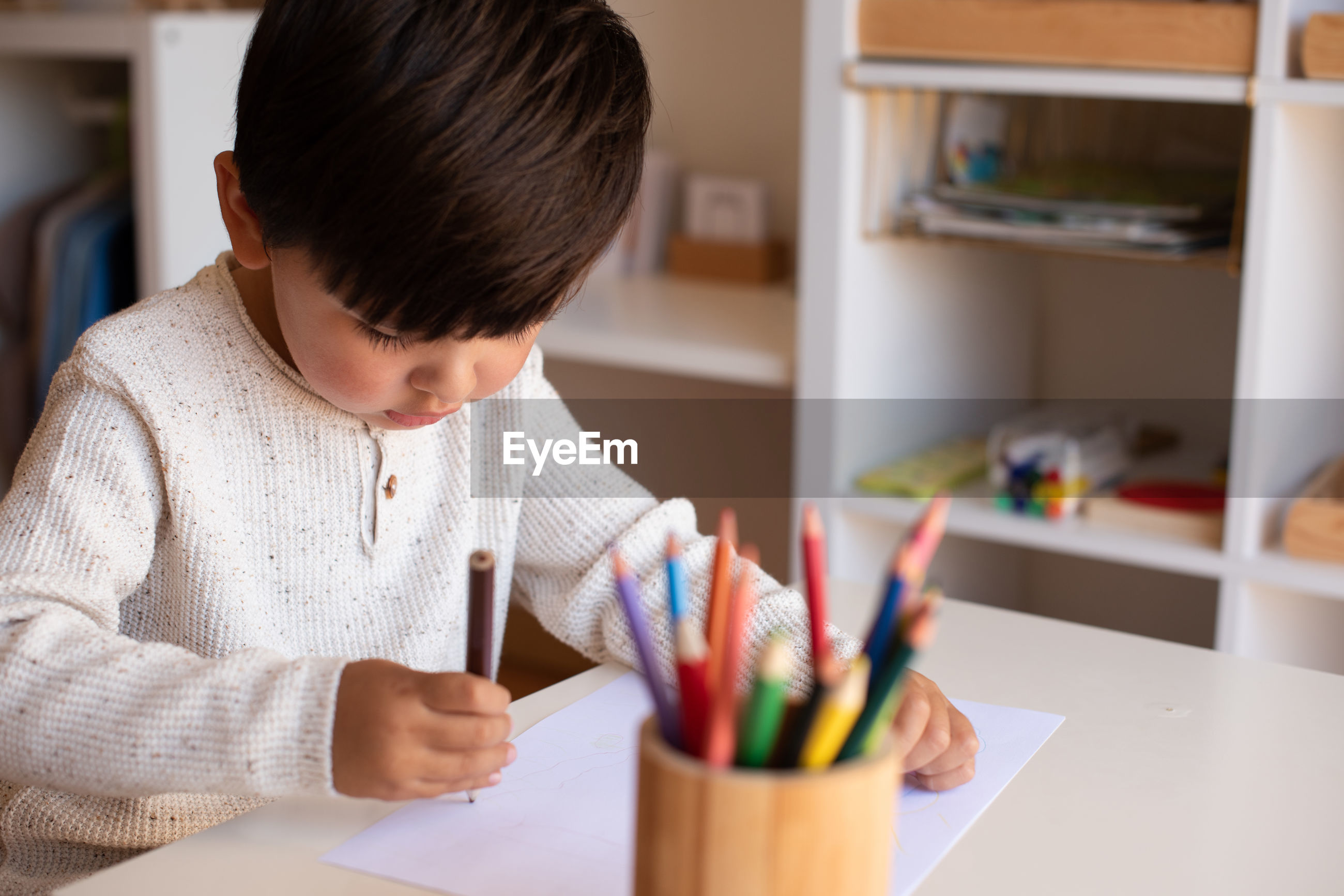Cute boy drawing on paper at home