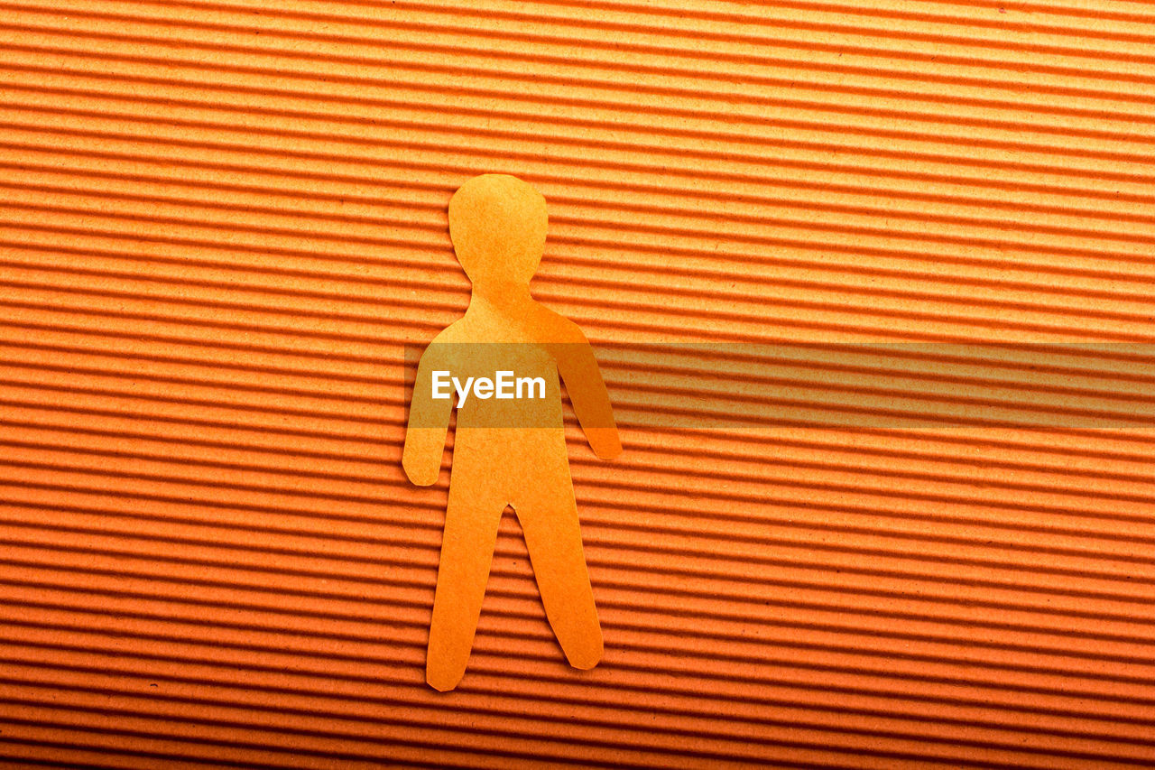 no people, close-up, indoors, pattern, representation, human representation, male likeness, yellow, striped, studio shot, single object, orange color, sign, creativity, day, backgrounds, wall - building feature, still life