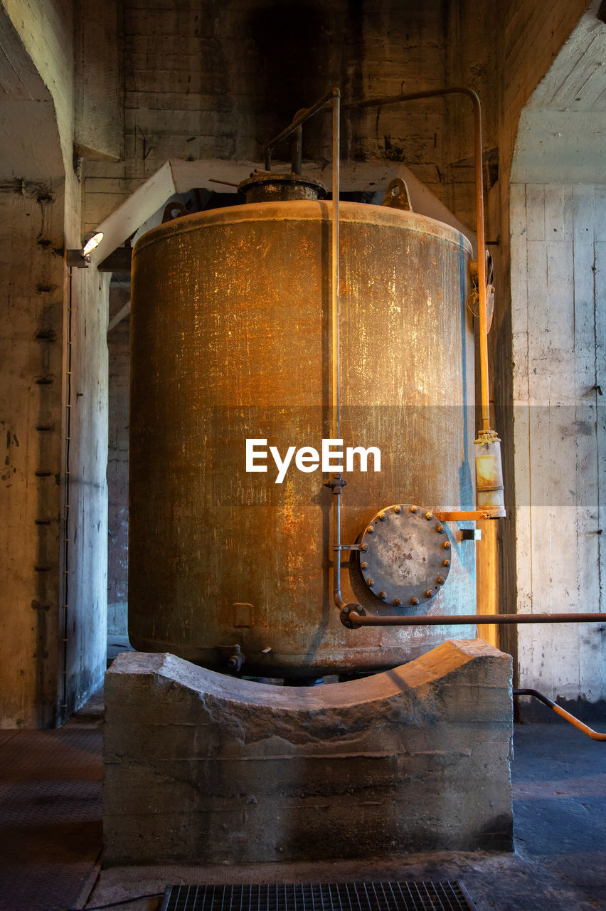 indoors, wood - material, no people, metal, old, domestic room, household equipment, cylinder, barrel, kitchen utensil, industry, container, day, cellar, furnace, food and drink industry, factory, food and drink, abandoned, winemaking, distillation